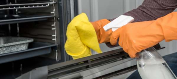 man-s-hand-gloves-cleaning-kitchen-oven-housework@2x
